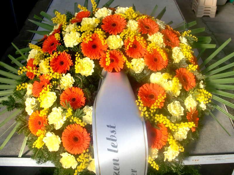 22 Trauerkranz mit gelben Nelken und orangen Gerbera und Mimose